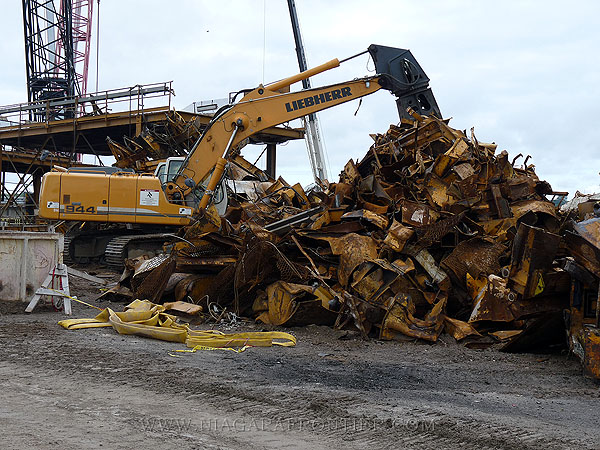 A hydraulic scrap cutter making easy prey of the Invert Carrier - cutter uses 3000 tons pressure to cut steel